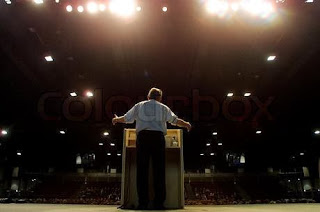 539618-543738-rear-view-of-man-giving-speech-from-stage-to-people.jpg